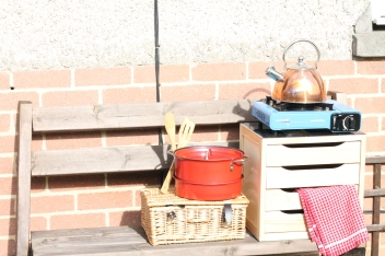 Nesting pans, shiny kettle and drawers with various bits and bobs.