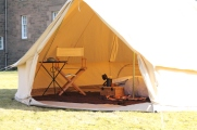 4 metre canvas bell tent, set up with double bed, table and chair.